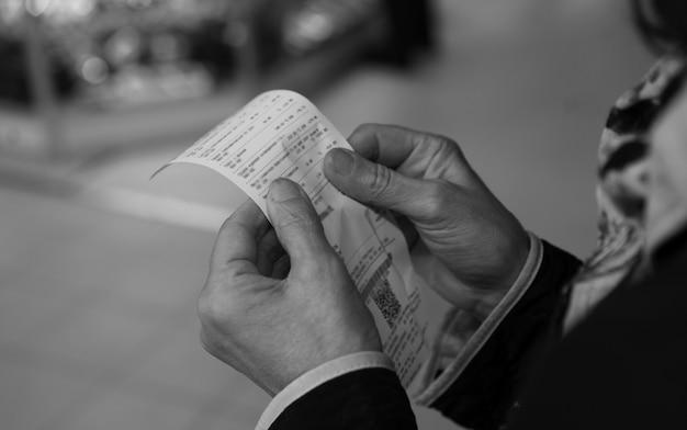 Frau hält einen einkaufsscheck in ihren händen