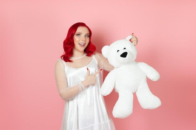 Frau hält einen großen weißen teddybär am ohr und zeigt mit dem zeigefinger darauf