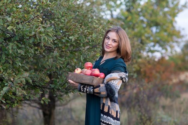Frau hält einen korb mit roten äpfeln