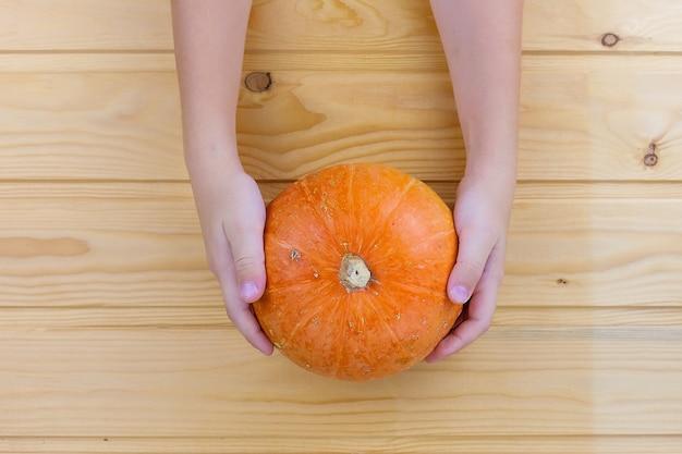 Frau hält einen kürbis. weibliche hände mit trendiger herbstmarmormaniküre in orange farbe