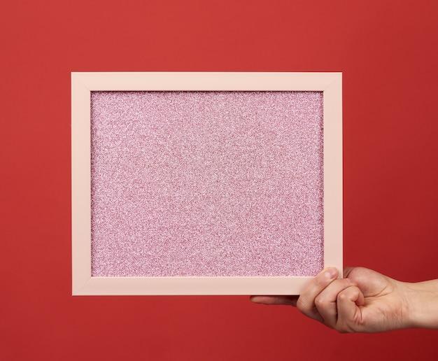 Frau hält einen leeren rosa rahmen auf einem roten hintergrund, platz für eine inschrift
