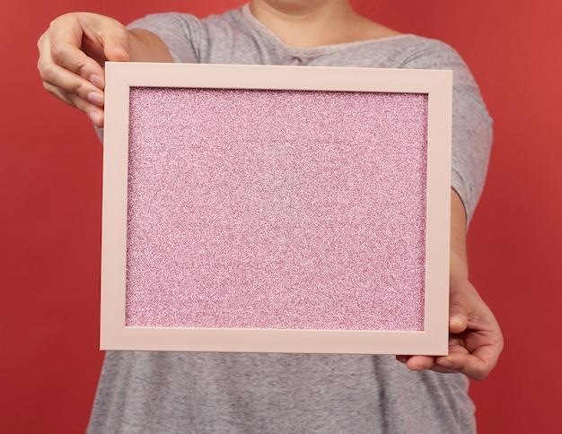 Frau hält einen leeren rosa rahmen auf einem roten hintergrund