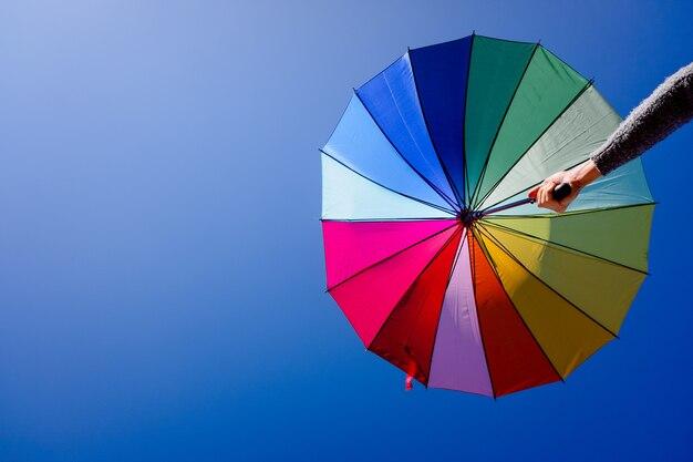 Frau hält einen mehrfarbigen sonnenschirm an einem sommertag mit blauem himmel