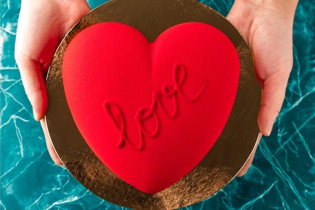 Frau hält einen roten samtkuchen in form eines herzens mit der aufschrift liebe