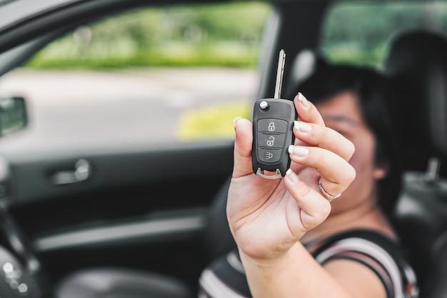 Frau hält einen schlüssel auto in ihren händen