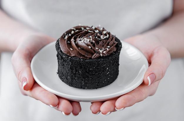 Frau hält einen teller schokoladenkuchen in ihren händen. hausgemachte desserts.