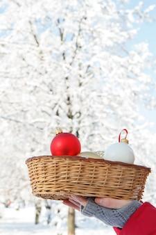 Frau hält einen weidenkorb mit weihnachtskugeln im winterstadtpark mit schneebedeckten bäumen im hintergrund. weihnachts- oder neujahrskomposition.