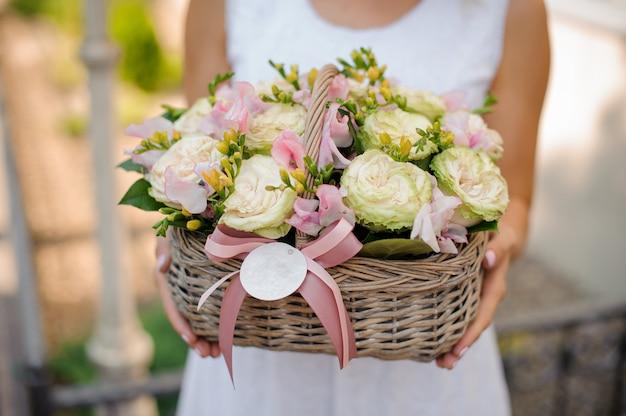 Frau hält einen weidenkorb voller rosen und ranunkulus