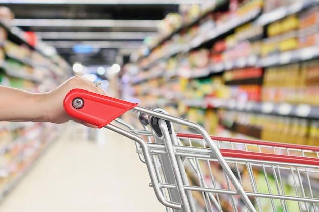 Frau hält einkaufswagen mit abstraktem unschärfe-supermarkt-discounter-gang und produktregalen innen defokussiertem bokeh-hintergrund
