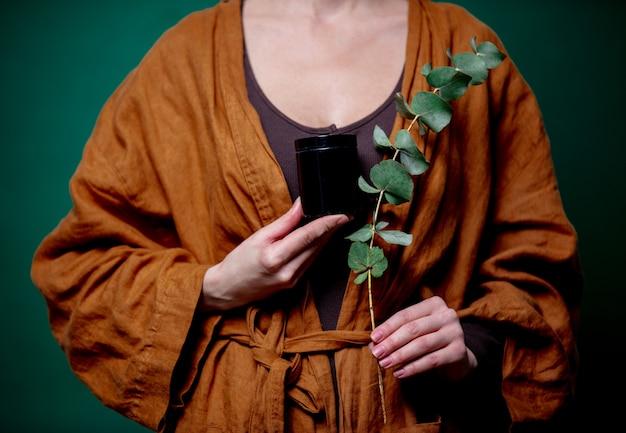 Frau hält eukalyptuszweig und schwarzes glas