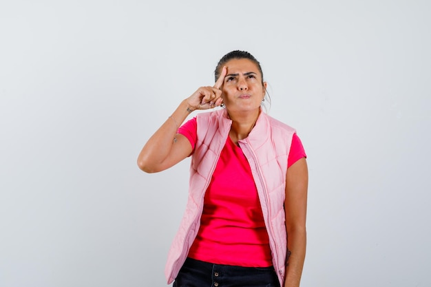 Frau hält finger im gesicht in t-shirt, weste und sieht nachdenklich aus
