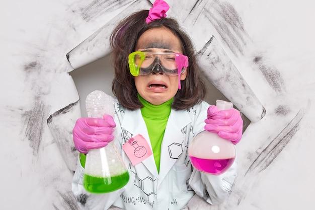 Frau hält flaschen mit flüssigkeit macht laborstudien trägt schutzbrille weiße mantelgummihandschuhe posiert im papierloch. chemieindustrie