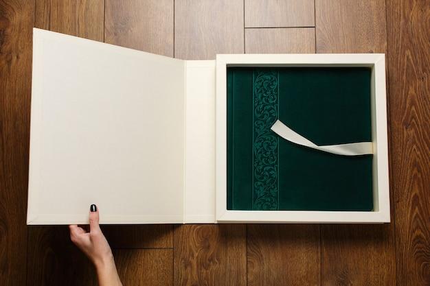 Frau hält fotobuch mit grünem umschlag im karton. person offenes fotoalbum mit wildlederbezug