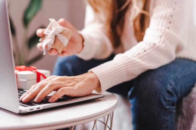Frau hält geschenk, das am laptop tippt. urlaub online-shopping
