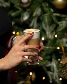 Frau hält glas latte macchiato mit schaum