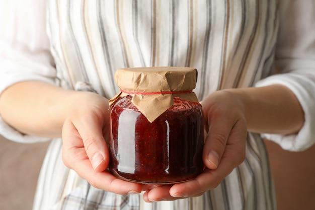 Frau hält glas mit erdbeermarmelade, nahaufnahme