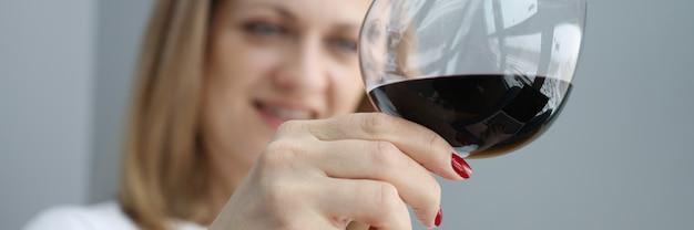 Frau hält glas rotwein in der hand