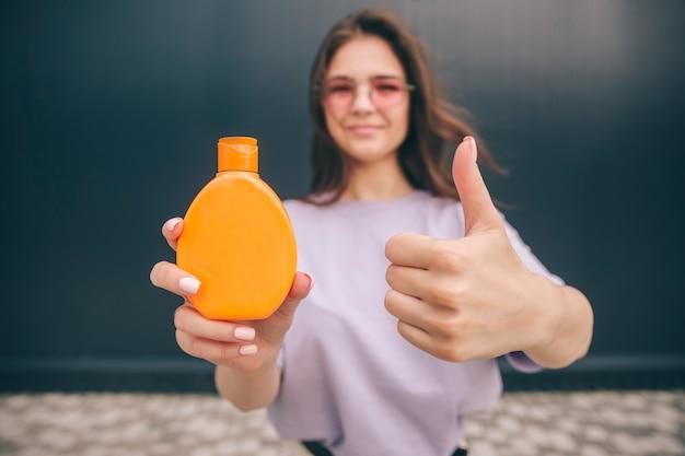 Frau hält große hände hoch und zeigt orange flasche mit sonnenschutz-spf-schutz im inneren