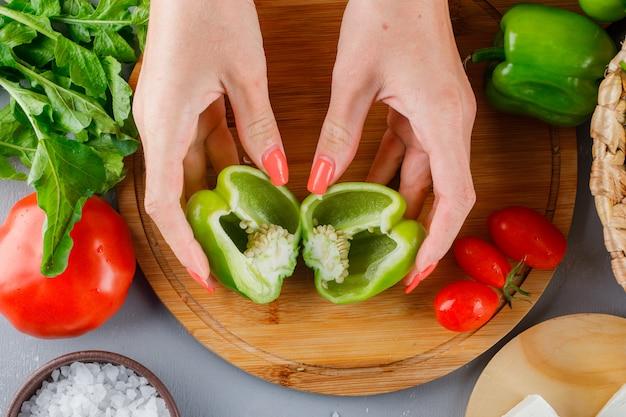 Frau hält grünen pfeffer halbiert auf einem schneidebrett mit tomaten, salz und käse