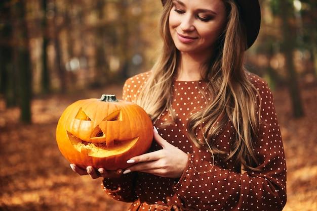 Frau hält gruseligen kürbis für halloween
