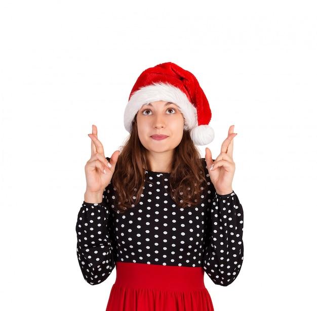 Frau hält hände hoch, daumen drücken und träumt von etwas. emotionales mädchen im weihnachtsmann-weihnachtshut lokalisiert auf weißem hintergrund. urlaub