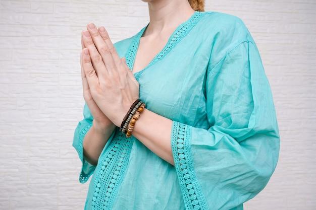 Frau hält hände im gebet und in der dankbarkeitsgeste zusammen