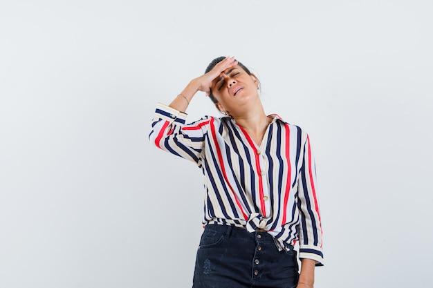 Frau hält hand über augen in hemd, rock und sieht müde aus.