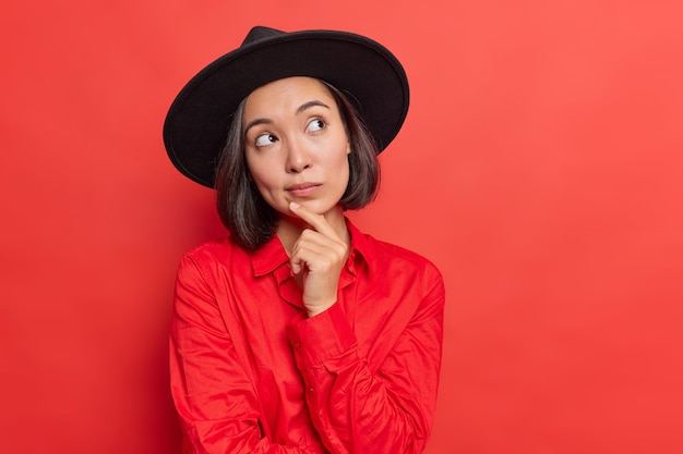Frau hält handon kinn tief in gedanken versunken denkt, dass etwas modisches schwarzes huthemd trägt, posiert auf rot