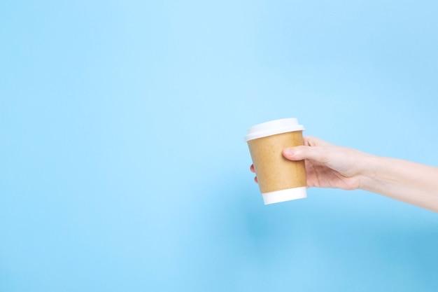 Frau hält handpapierbecher mit kaffee auf blauem hintergrund. speicherplatz kopieren