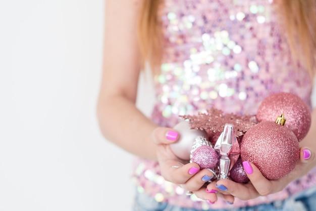 Frau hält handvoll roségold glitzernde kugeln.