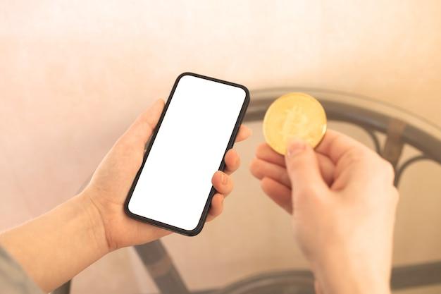 Frau hält handymodell und eine bitcoin, konzept der modernen zahlungsweise, kopienraumfoto