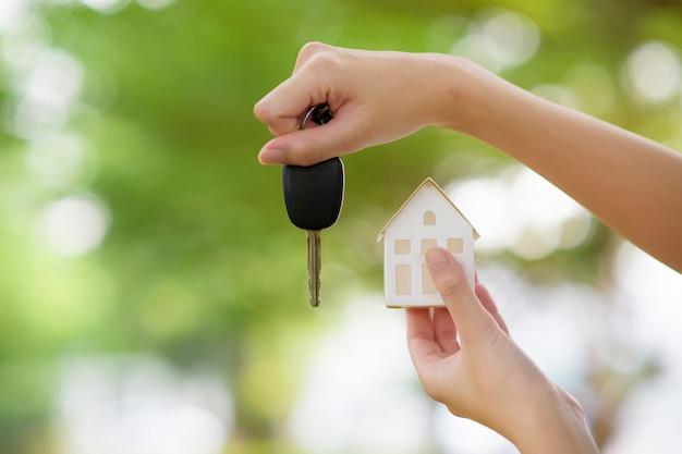 Frau hält haus und autoschlüssel auf grün