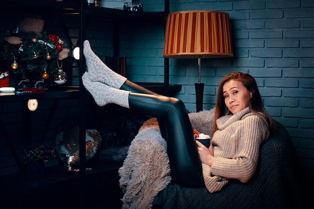 Frau hält heiße schokolade mit marshmallows auf stuhl weihnachtsbaum mit dekorationen auf sch...