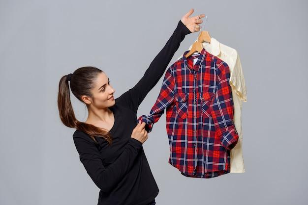 Frau hält hemden und wählt, welches outfit sie trägt