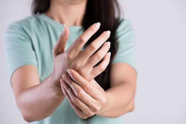 Frau hält ihre handgelenkhandverletzung und glaubt den schmerz. gesundheitsversorgung und medizinisches konzept.