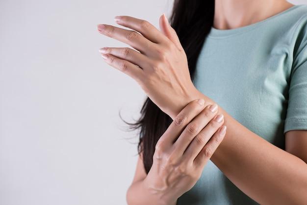 Frau hält ihre handgelenkhandverletzung und glaubt den schmerz.