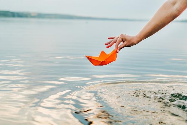 Frau hält im sommer ein papierboot an den fingern über dem fluss.