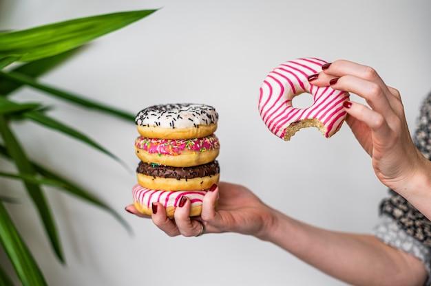 Frau hält in der hand bunten stapel glasierte donuts. weißer hintergrund. ansicht von oben. platz kopieren.