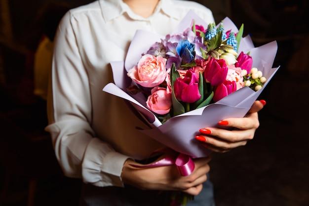 Frau hält in der hand einen prächtigen blumenstrauß mit bunten frischen blumen. ein tolles geschenk für jeden anlass.