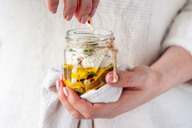 Frau hält in ihrer hand transparentes glas mit scheiben von weißem weichkäse in olivenöl