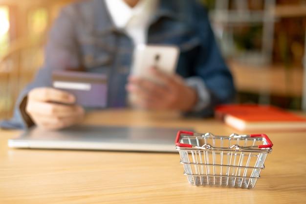 Frau hält kreditkarte und verwendet smartphone. online-shopping-konzept.