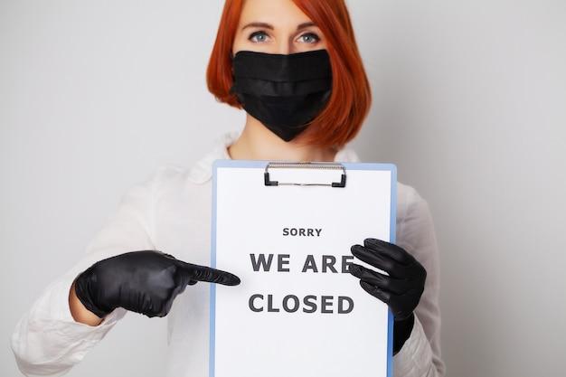 Frau hält leer mit inschrift wir sind geschlossen und fordern die verbreitung von covid-19 zu stoppen
