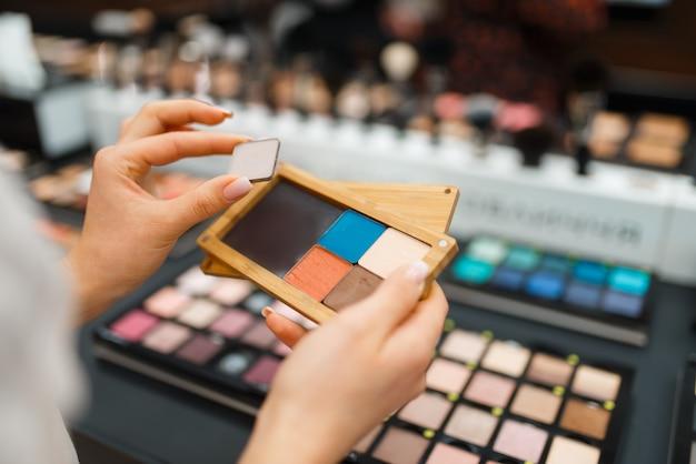 Frau hält lidschatten am regal im kosmetikladen. käufer an der vitrine im luxus-beauty-shop-salon, kundin im modemarkt