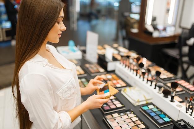 Frau hält lidschatten am regal im kosmetikladen. käufer an der vitrine im luxus-schönheitssalon, kundin im modegeschäft
