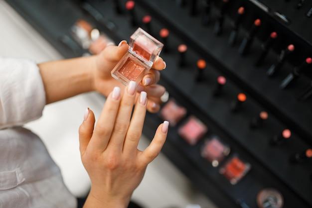 Frau hält lippenstifttester im kosmetikgeschäft. käufer an der vitrine im luxus-beauty-shop-salon, kundin im modemarkt