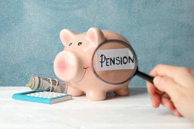 Frau hält lupe auf sparschwein mit inschrift pension gegen blau