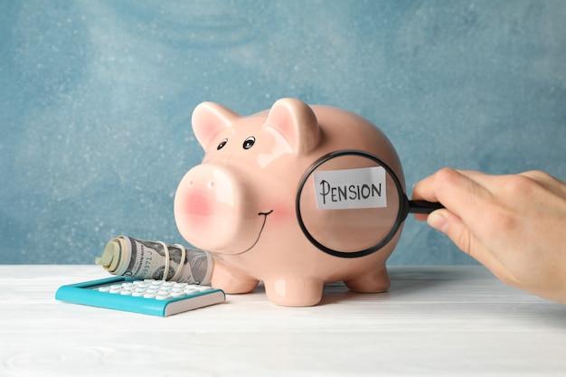 Frau hält lupe auf sparschwein mit inschrift pension gegen blaue oberfläche