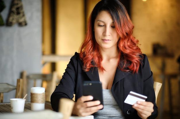 Frau hält mit einer hand ihr telefon und in der anderen hand eine kreditkarte