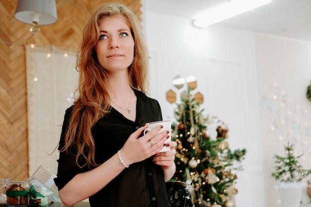 Frau hält morgens eine tasse kaffee in der weihnachtsküche. glückliche junge frau, die spaß hat und lächelt