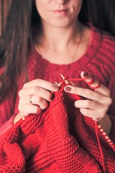 Frau hält nadeln und strickt eine rote warme jacke